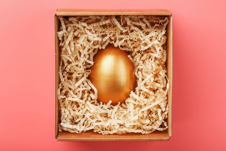 Golden egg in a box with shavings on a pink background. The concept of individuality, exclusivity, best choice, prize, special surprise, rare gift. Stylish decor with minimal concept.