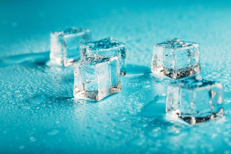 Ice cubes are scattered with water drops scattered on a blue background. Refreshing ice.