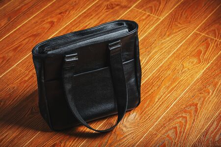 Handmade black leather bag on a wooden background, made of natural material. Design, Hobbies and businesses.
