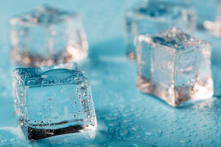 Ice cubes are scattered with water drops scattered on a blue background. Close up. Refreshing ice.