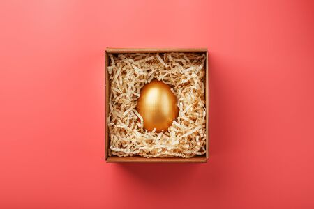 Golden egg in a box on a pink background. The concept of exclusivity, best choice, prize, special surprise, expensive gift. Minimalistic concept.