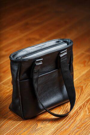 Sac en cuir noir fait à la main sur un fond en bois, en matériau naturel. Design, Loisirs et entreprises.