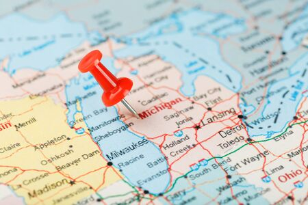 Red clerical needle on a map of USA, Michigan and the capital Lansing. Close up map of Michigan with red tack, United States map pin USA Foto de archivo