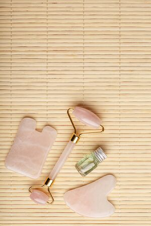 Gua sha massage made of natural rose Quartz-roller, jade stone and oil, on a bamboo background for face and body care. Copy the space for your text. Chinese medicine.