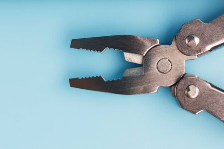 The multitool multi-function tool hovers on a blue background. The concept of an expanded multi-tool with free space. Clipping path included isolate