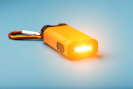 Orange led Flashlight with a carabiner on a blue background. LED lights in flight. Free space for text. Concept
