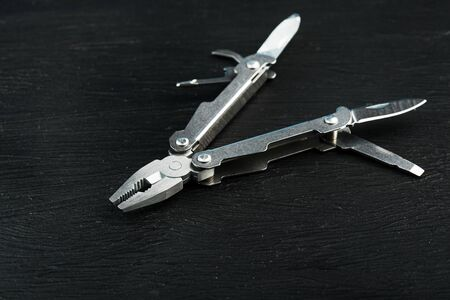 Multitool is a multi-functional tool on a black background. The concept of an expanded multi-tool with free space. Clipping path included isolate