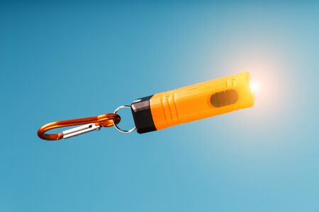 An orange led flashlight with a carabiner glows on a blue background. Led lights in flight. Free space for text. Concept
