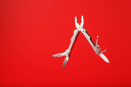 Multitool is a multi-functional tool on a red background. The concept of an open, flying multi-tool with free space. Clipping path included isolate Stockfoto