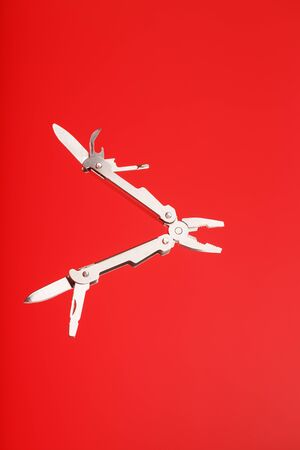 Multitool is a multi-functional tool on a red background. The concept of an open, flying multi-tool with free space. Clipping path included isolate