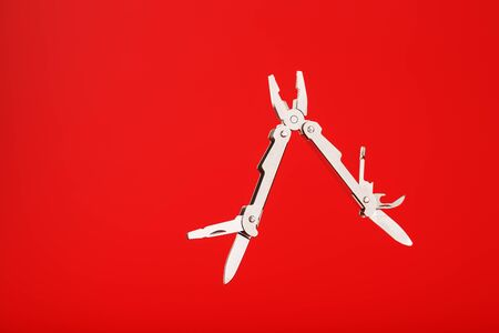 Multitool is a multi-functional tool on a red background. The concept of an open, flying multi-tool with free space.