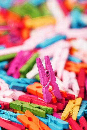 Small Clothespins of different colors close-up as a texture and background in full screen. Decorative clothespins for creativity.