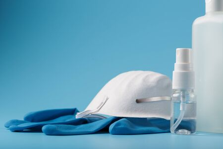 Anti-virus protection kit on a blue background, mask, rubber gloves, hand sanitizer bottles, antiseptic gel. Isolate, a minimalistic concept