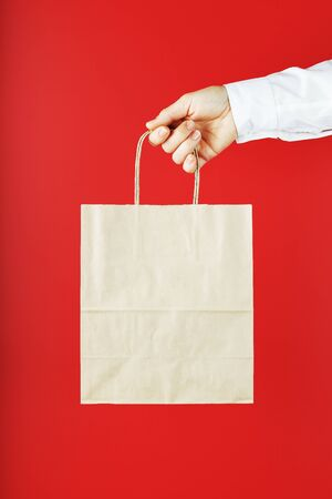 Paper bag at arms length isolated on a red background. Layout of the packaging template with space for copying, advertising. The concept of providing services and assistance, purchase in a store