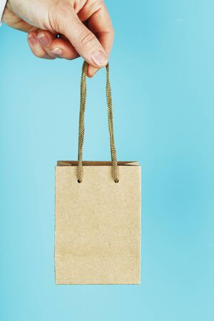 Small paper Bag at arms length, brown craft bag for takeaway isolated on blue background. Packaging template layout with space for copying, advertising. Concept of assistance, delivery service. 版權商用圖片