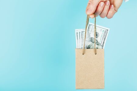 A small paper bag for financial aid and support made of paper at arm's length with US dollars on a blue background. The concept of negligible financial support in business, the population and entrepreneurs. The concept of financial assistance.Dollar bill