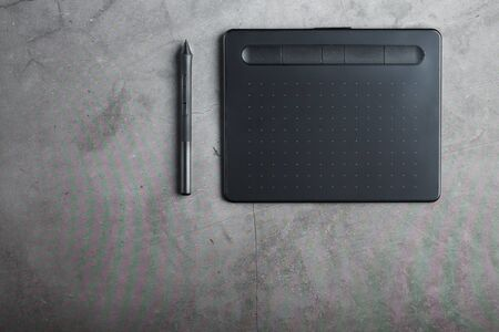 Graphic tablet with a stylus on a dark textural background, top view. Gadget for working as a designer, artist and photographer. Banco de Imagens