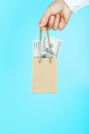A small paper bag in hand with US dollars on a blue background. Layout of the packaging template with space for copying, advertising. The concept of financial assistance. 스톡 콘텐츠 - 144271985