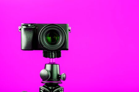 Professional camera on a tripod, on a pink background. Record videos and photos for your blog or report. Free space, isolated.