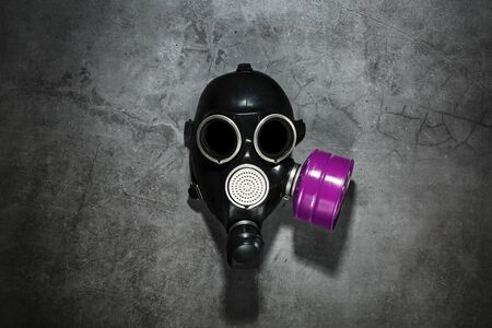 Gas mask on a black stone background with a pink filter cartridge. Post-apocalyptic concept. Free space, top view.