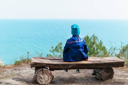 A lonely child is resting on a bench in the forest with a view of the sea. The concept of loneliness, freedom and isolation.