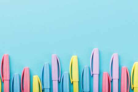 Multi-colored markers on a blue background with free space. Minimalistic concept
