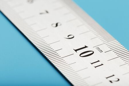 Metal ruler on a blue background close-up with a copy of the space for your text. Isolate