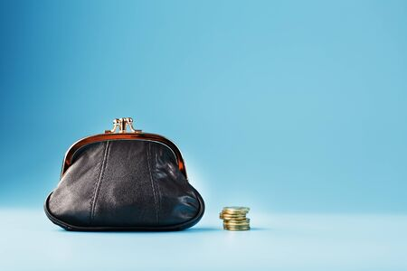 Black wallet with coins on a blue background. Budget for investment in the future. Free space, isolate