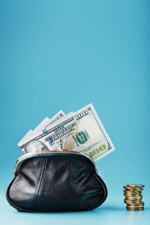 Black wallet with coins and dollars on a blue background. Budget for investment in the future. Isolate, close-up