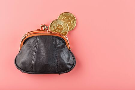 Classic black wallet with bitcoin coins on a pink background. Stockfoto