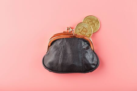 Classic black wallet with bitcoin coins on a pink background. Minimalistic concept. Free space, top view