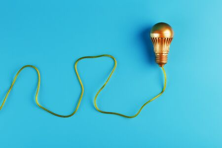 A gold light bulb with a gold wire on a blue background. The view from the top.