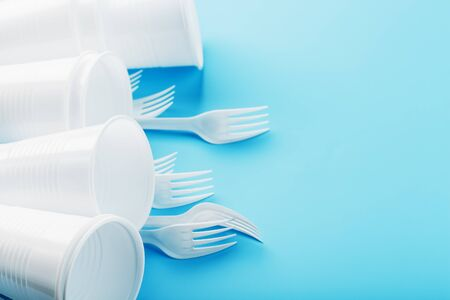 Dishes made of white plastic on a blue background. Free space. The view from the top Reklamní fotografie