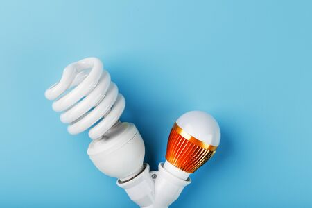 Gold LED light bulb and energy-saving in a double base on a blue background. The view from the top Standard-Bild - 147096817