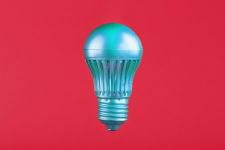 The light bulb hovers in the center of the frame in an isolated space on a pink background. Minimalistic style with conceptual ideas. To be different