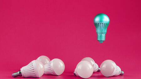 A special Light bulb hovers over simple, standard white light bulbs on a pink background. Minimalistic style with conceptual ideas. Be different
