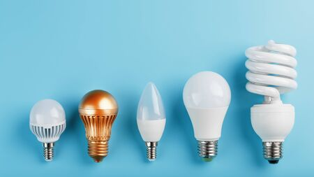 One Golden light bulb in a row of energy-saving white lamps on a blue background. The view from the top