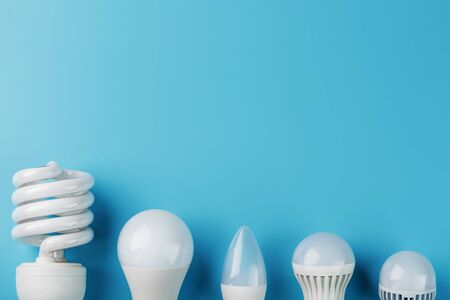 Energy-Saving light bulbs are arranged in a row on a blue background, top view. Progress of led lamps. Standard-Bild