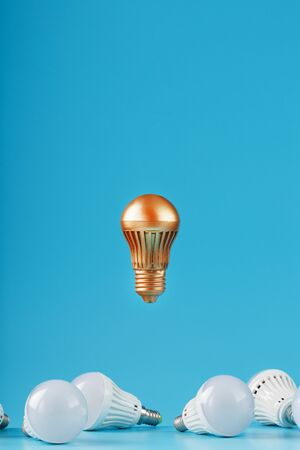 The Golden light bulb rises and hovers above the surroundings of ordinary light bulbs. A conceptual idea, the contrast of surrounding competitors. Minimalism. 版權商用圖片