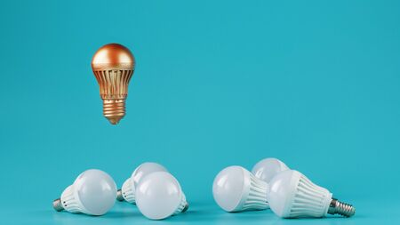 A prominent gold light bulb levitates above an environment of white led bulbs. The concept of an unusual idea and the contrast of surrounding rivals. Minimalism.