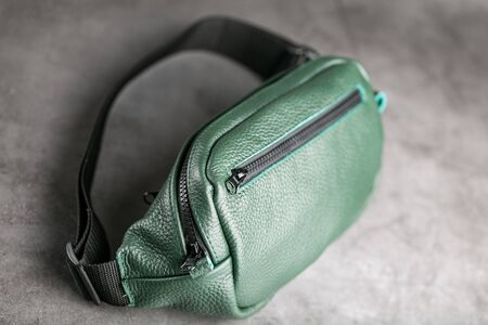 Belt bag made of dark green textured leather, banana on a gray background. Handmade