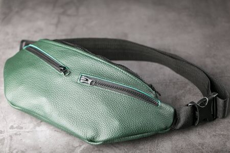 Belt bag made of dark green textured leather, banana on a gray background. Handmade Фото со стока