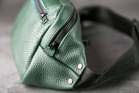 Belt bag made of dark green textured leather, banana on a gray background. Handmade Stockfoto