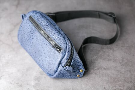 Waist bag made of blue leather, banana on a gray background. Handmade