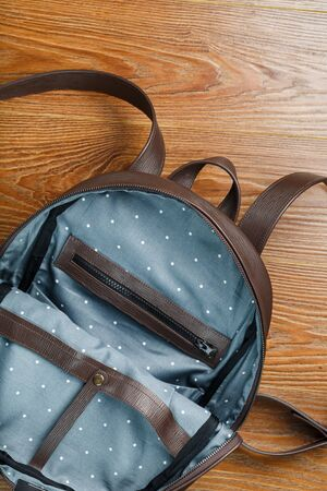 An empty handmade genuine leather backpack is open for things. Close-up, Studio light.
