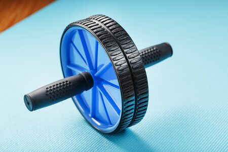 Sports roll for training muscles and abs on the blue Mat. Sports at home