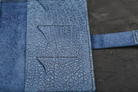 Blue leather wallet on a black textured background. Handmade work