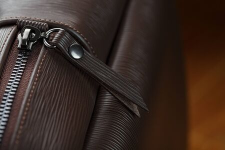 Close-up elements and details of the Backpack made of brown genuine leather on a wooden background. Classic style, handmade.