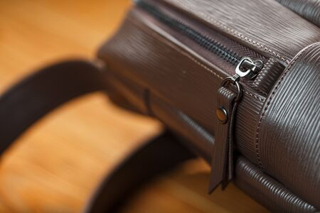 Close-up of the elements of the bag, backpack made of genuine leather with belt buckles and locks. Leather backpack or satchel made of brown leather on a wooden background. Handmade, Studio light.