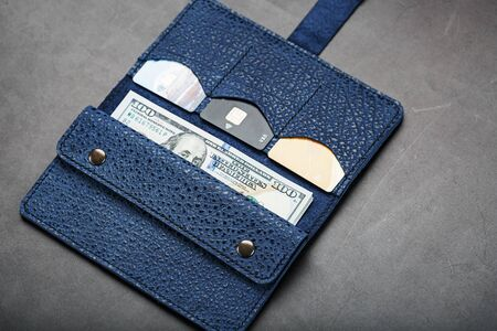 Leather Partman in blue with one hundred dollar bills and electronic credit cards on a black background. Handicraft. Business and Finance